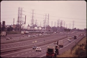 NEW_JERSEY_TURNPIKE_WITH_HUMBLE_OIL_COMPANY_TANKS_AND_HIGH_VOLTAGE_ELECTRIC_TOWERS_IN_THE_BACKGROUND_-_NARA_-_552001